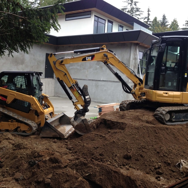 Heavy equipment shaping a yard